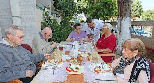 קבוצת קשישים נהנת מארוחה בחצר מרכז יום לקשיש