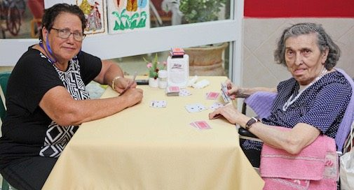 זוג נשים מבוגרות משחקות קלפים ומדברות על קצבת זקנה